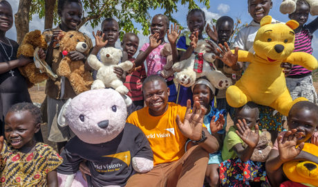 Moses Mukitale, Communication Coordinator of World Vision Uganda poses with children after they received Teddy Bears at Imvepi Refugee Settlement in Arua District in Northern Uganda 1 December 2017.